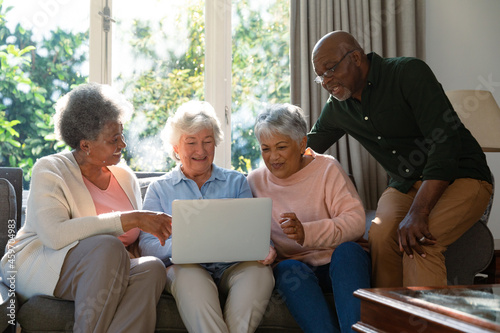 Three happy diverse senior woman and african american male friend sitting on sofa and using laptop