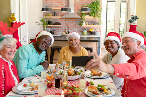 Diverse group of happy senior friends in holiday hats celebrating christmas together, taking selfie