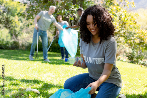 Smiling african american woman holding refuse sack, collecting plastic waste in field with friends