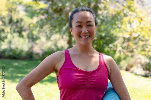 Happy fit korean woman holding yoga mat and looking at camera