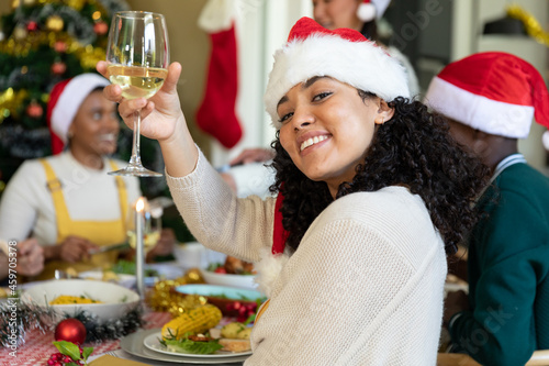 Happy mixed race woman in santa hat toasting, celebrating christmas with friends at home