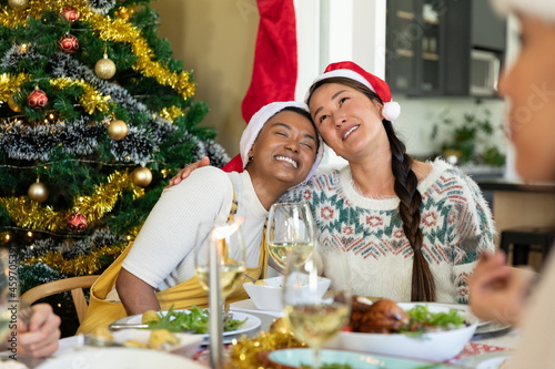 Happy diverse female friends in santa hats embracing, celebrating christmas with friends at home