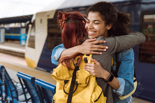 Canvas Print Multiracial two women hugging while saying goodbye at train station