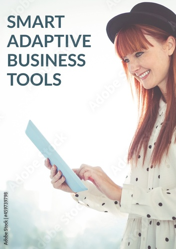 Composition of business tools text over caucasian woman using tablet and smiling