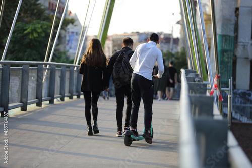 Mężczyzna jedzie na hulajnodze po moście we Wrocławiu.