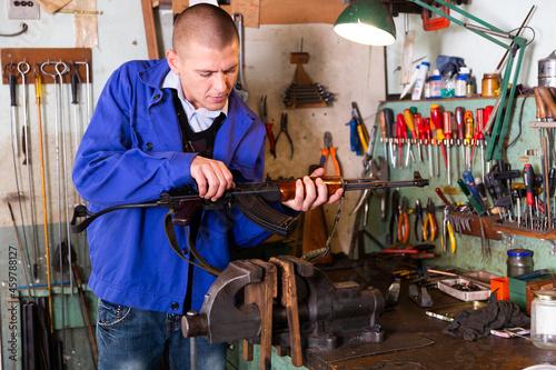 Fotografie, Obraz Gunsmith checks Kalashnikov assault rifle in a weapons workshop