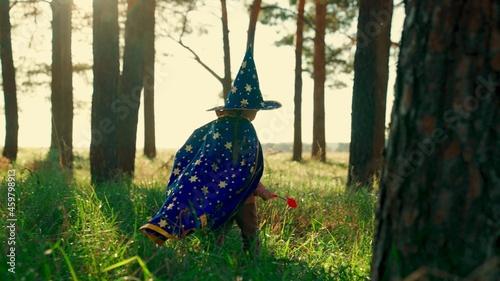 Obraz na plátně Child fantasies in mantle of magician in forest