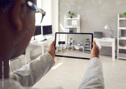 Leinwand Poster Black rental agent making photo presentation of apartment takes interior snaps using smart tablet device