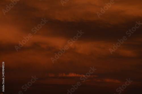Fotografie, Obraz Dark and dense summer storm clouds cover the landscape at sunset, touched by the
