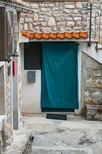 Split, Croatia A green curtain hags over a doorway on a narrow street Fototapet