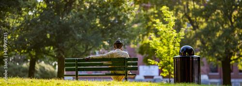 Billede på lærred Man in a hat sitting on a park bench  alone