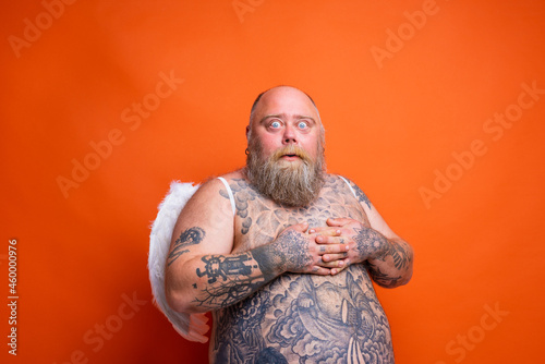 Fototapeta Fat amazed man with beard ,tattoos and wings acts like an angel