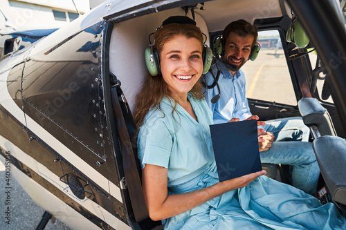 Foto Joyful woman and aviation tutor posing for camera in chopper