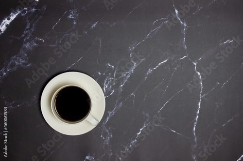 Murais de parede A cup of coffee on a black marble table with copy space.
