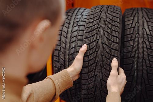 Slika na platnu Unrecognizable man chooses winter car tires in the auto shop