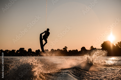 Canvastavla beautiful view of dark silhouette of active male rider holds rope and making extreme jump on wakeboard at sunset