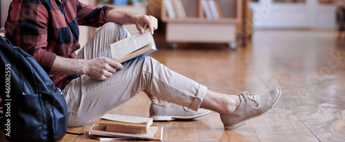 Canvas Handsome student in casualwear reading book or manual in college library