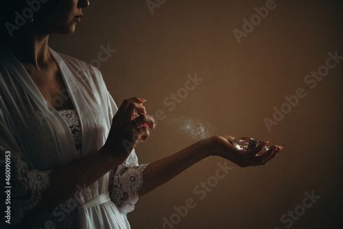 Canvas Print woman in a lacy white robe sprays perfume on her wrist