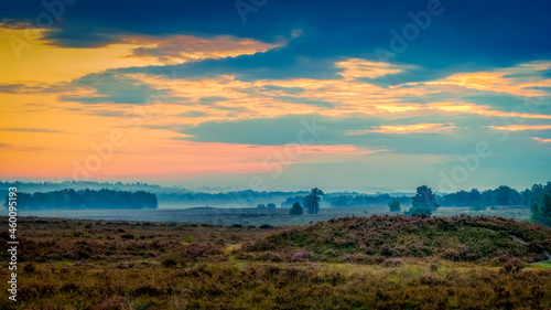 Obraz na plátně Sunrise with misty view of the veluwe valley in a typical Dutch moorland field