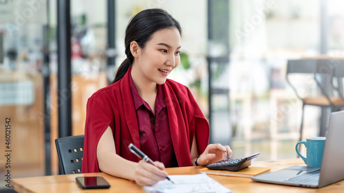 Foto Charming young Asian businesswoman wearing red dress working at the office