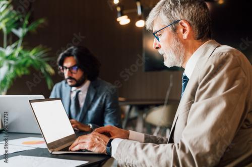 Foto Italy, Businessmen using laptops in creative studio