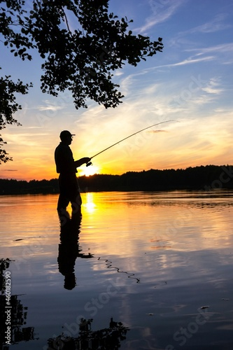 Fototapeta fisherman silhouette during sunset