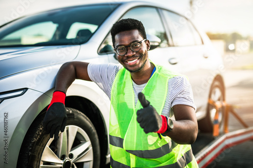 Fotografie, Obraz Handsome young African American man working in towing service on the road