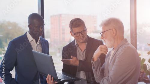 Billede på lærred three diverse business workgroup team with african man leader discuss paperwork