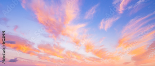 Stunning romantic and relaxing sunrise with some pink illuminated clouds moving across a blue sky. Long exposure, natural background.