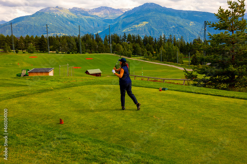 Wallpaper Mural Golfer Teeing Off on Crans Sur Sierre Golf Course with House and Mountain View in Crans Montana in Valais, Switzerland