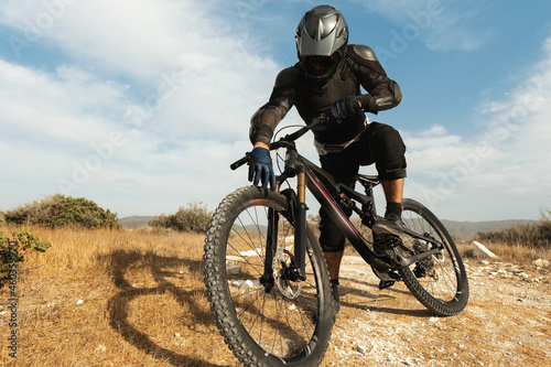 Downhill rider fully equipped with protective gear and his bicycle Fototapet