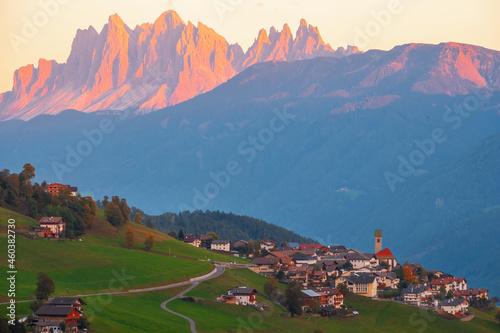 Fotografie, Obraz Cozy little mountain village on the hilltop, Dolomites mountains in the backgrou