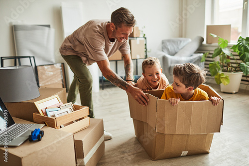 Fototapeta Portrait of modern father playing with two boys in cardboard box while family mo