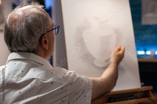 Obraz na plátně Caucasian elder artist working on vase masterpiece in artistic workspace