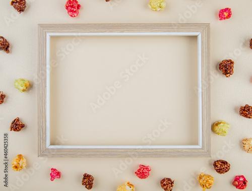 Fotografija top view of white frame with skittles popcorn around on white background with co