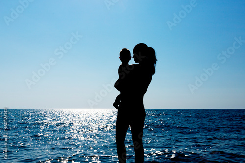 A young girl holds a child in her arms against the sun Fototapeta