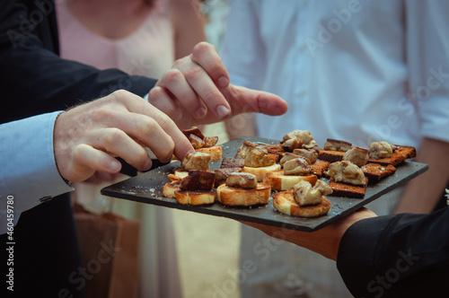 Toasts de foie gras chaud - les mains prennent les mise en bouche sur un plateau Fototapet
