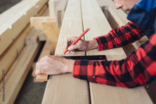 Canvas Print Hands of a carpenter using a right angle tool or square