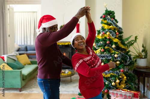 Happy african american senior couple in santa hats dancing at home at christmas time