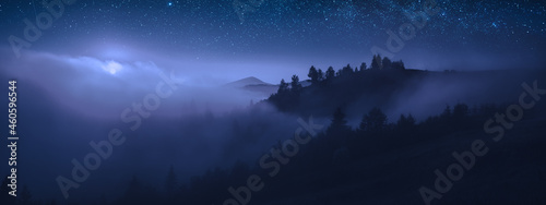 Canvas Print Beautiful moonrise over the foggy mountains at night