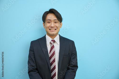 青背景の前で爽やかに笑うスーツを着た日本人男性 Fototapet