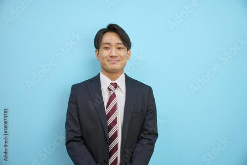 Fotografering 青背景の前で爽やかに笑うスーツを着た日本人男性