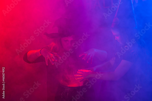 Fotografie, Tablou Two halloween witches making a potion and conjure in halloween night