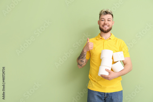 Fotografia, Obraz Young man with many rolls of toilet paper showing thumb-up on color background