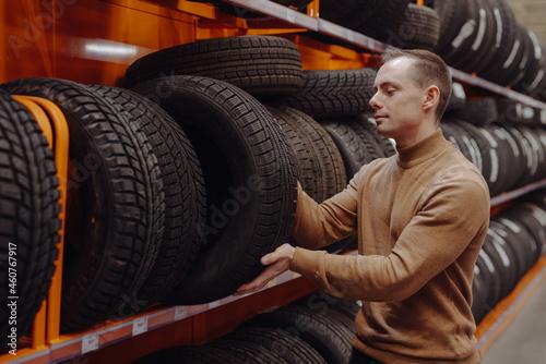Fotografija Man chooses winter car tires in the auto shop