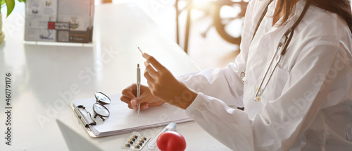 Foto Asian female doctor or pharmacist writes a medication prescription