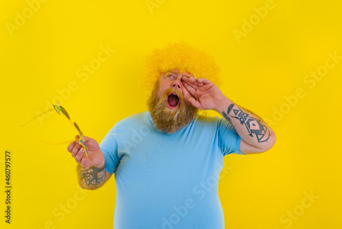 Fotografiet Fat annoyed man with wig in head and sunglasses