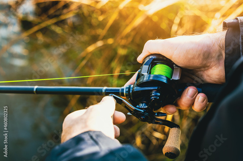 Fototapeta fishing rod with multiplier reel and green braided line in angler hands
