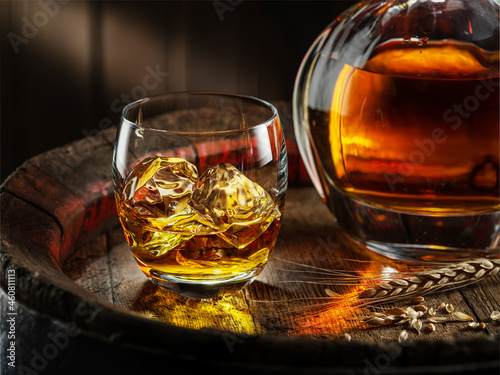 Murais de parede Carafe of whisky and glass of whisky on old wooden cask at the dark background