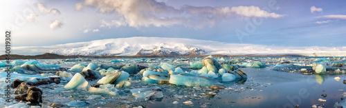 Fotografie, Obraz Panorama of blue glacial ice floating in the Jokulsarlon Lagoon, Iceland in winter